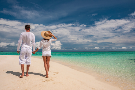 Couple in white walking on a tropical beach at Maldives photo