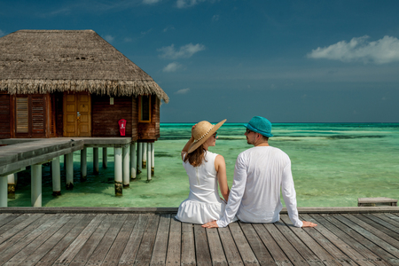 Couple on a tropical beach jetty at Maldives photo