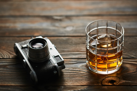 Glass of whiskey and vintage old 35mm rangefinder camera on wooden background Stock Photo