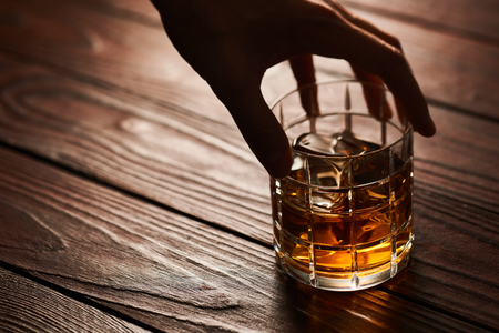 Mans hand holding Glass of whiskey with ice cubes on rustic wooden table with copy-space Stock Photo
