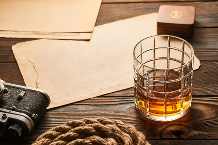 Glass of whiskey and vintage old 35mm rangefinder camera on wooden background with antique XIX century map Stock Photo