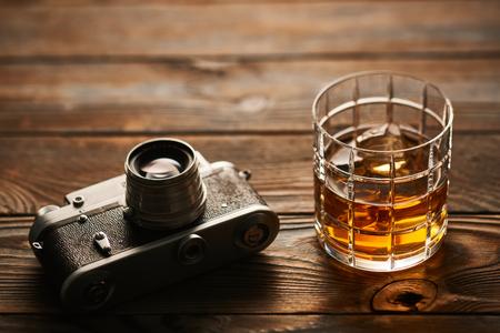 rangefinder: Glass of whiskey and vintage old 35mm rangefinder camera on wooden background Stock Photo