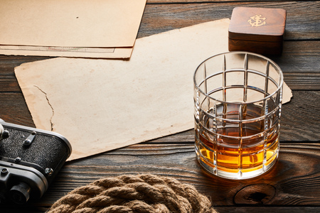 rangefinder: Glass of whiskey and vintage old 35mm rangefinder camera on wooden background with antique XIX century map Stock Photo