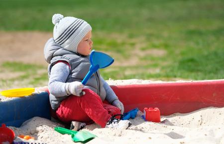 Portrét batole dítě nosit vestu bunda venku. Jeden rok starý chlapeček hraje s pískem na pískoviště dětského hřiště Reklamní fotografie