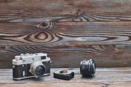rangefinder: Vintage old retro 35mm rangefinder camera, lens and light meter on wooden background with copy space