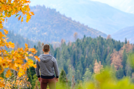Tourist man hiking in Sequoia National Park at fall, looking at autumn mountain scenic landscape. California, United States. photo