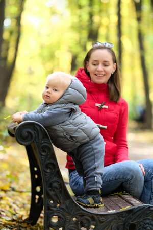 Portrait of toddler child in warm vest jacket outdoors. One year old baby boy in autumn park with his mother photo