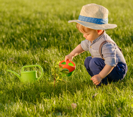 Portrait of toddler child outdoors. Rural scene with one year old baby boy wearing straw hat using watering can Standard-Bild