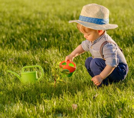 Portret van peuter kind buitenshuis. Landelijke scène met een jaar oude babyjongen die strohoed draagt ??met waterkruik Stockfoto - 83406518