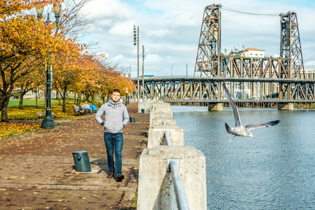 Man walking along the riverwalk in Portland city at autumn, Oregon, USA. photo