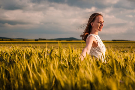 Beautiful woman in white dress on golden yellow wheat field in warm sunshine under dramatic sky, fresh vibrant colors, at Rhine Valley (Rhine Gorge) in Germany photo