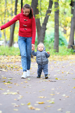 Portrait of toddler child in warm vest jacket outdoors. One year old baby boy in autumn park learning to walk with his mother