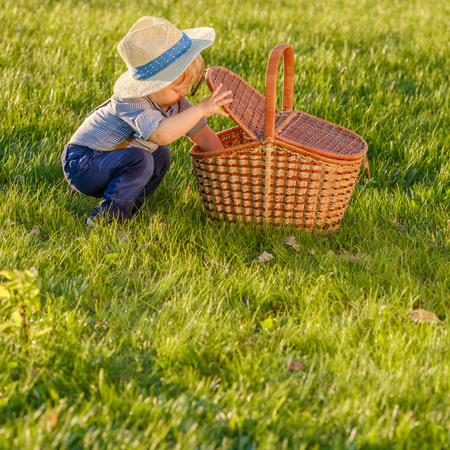reggicalze: Portrait of toddler child outdoors. Rural scene with one year old baby boy wearing straw hat looking in picnic basket