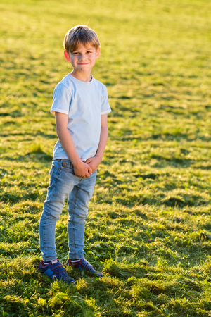 Little boy outdoors smiling in the park at summer