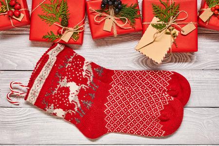 Creatief verpakte en verfraaide Kerstmis stelt in dozen en kousen op witte houten achtergrond voor Hoogste mening van hierboven. Ruimte kopiëren.