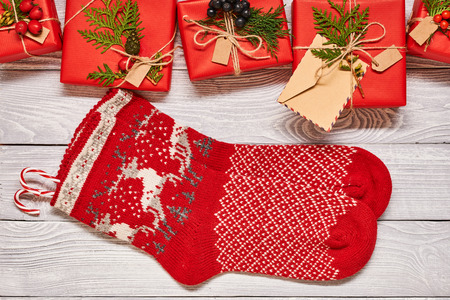 Kreativ eingewickelte und verzierte Weihnachtsgeschenke in den Kästen und in den Strümpfen auf weißem hölzernem Hintergrund Draufsicht von oben. Platz kopieren Standard-Bild