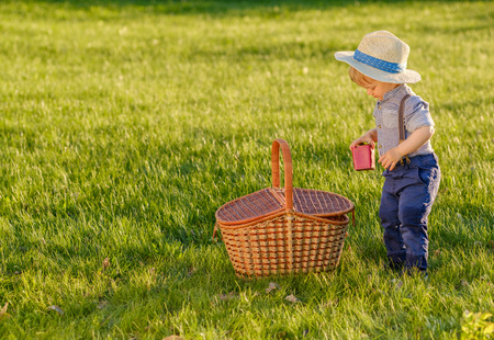 reggicalze: Portrait of toddler child outdoors. Rural scene with one year old baby boy wearing straw hat and picnic basket