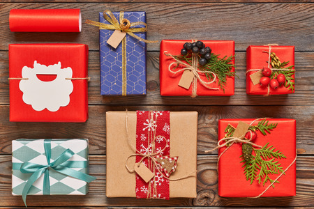 Creatively wrapped and decorated christmas presents in boxes on wooden background.Top view from above. Flat lay.