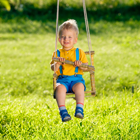 reggicalze: Portrait of toddler child swinging outdoors. Rural scene with one year old baby boy at swing. Healthy preschool children summer activity. Kid playing outside.