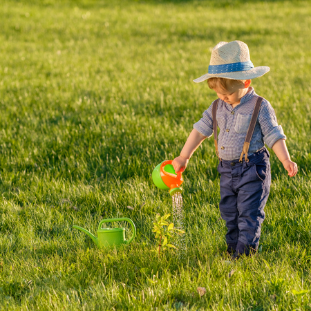 Portrait of toddler child outdoors. Rural scene with one year old baby boy wearing straw hat using watering can Stock Photo