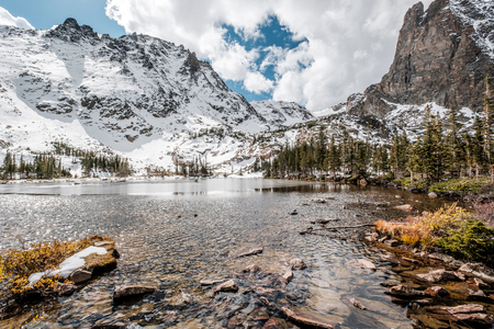 Lake Helene with rocks and mountains in snow around at autumn with cloudy sky. Rocky Mountain National Park in Colorado, USA. Stock Photo