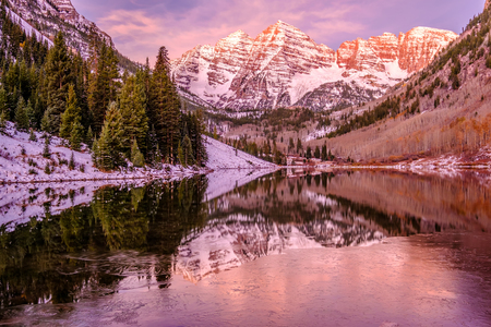 Maroon Bells and Maroon Lake with reflection of rocks and mountains in snow at sunrise around at autumn in Colorado, USA.