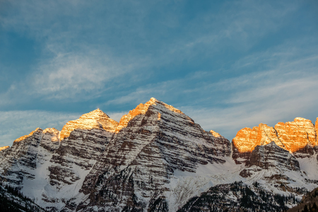 Maroon Bells mountains in snow at sunrise in Colorado, USA.