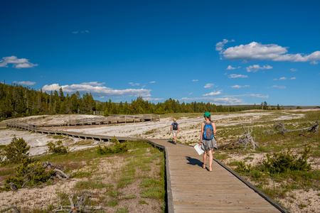 Tourists with backpack hiking in Yellowstone National Park near Firehole River, Wyoming, USA Stock Photo