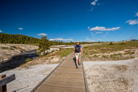 Tourist with backpack hiking in Yellowstone National Park near Firehole River, Wyoming, USA