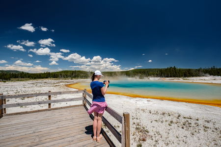 Woman tourist with camera overlooking hot thermal spring Sunset Lake in Yellowstone National Park, Black Sand Basin area, Wyoming, USA Stock Photo