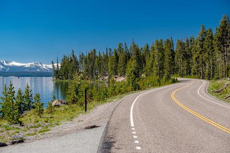 Highway by the lake in Yellowstone National Park, Wyoming, USA Stock Photo