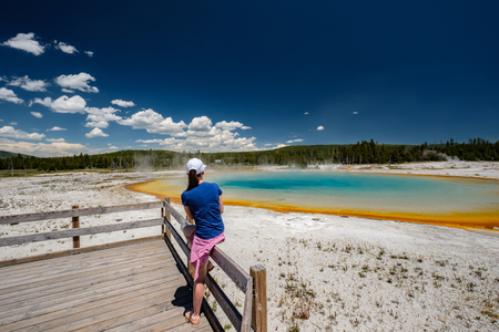 Woman tourist overlooking hot thermal spring Sunset Lake in Yellowstone National Park, Black Sand Basin area, Wyoming, USA Stock Photo