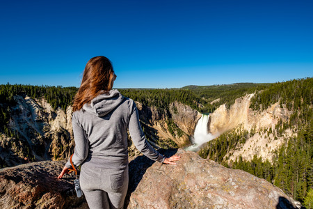 Woman tourist with camera overlooking Lower Falls waterfall in the Grand Canyon of Yellowstone National Park, Wyoming, USA