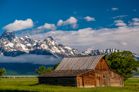 Old mormon barn in Grand Teton Mountains with low clouds. Grand Teton National Park, Wyoming, USA. Фото со стока
