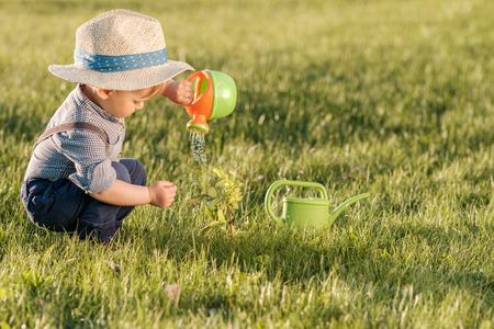 Portret van peuter kind buitenshuis. Landelijke scène met een jaar oude babyjongen die strohoed draagt ??met waterkruik