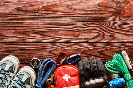 Travel items for hiking tourism still life over wooden background