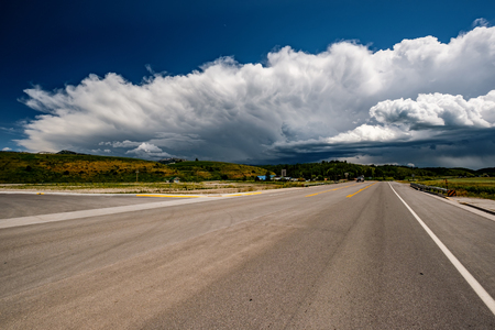 Empty open highway and stormy clouds in Wyoming, USA