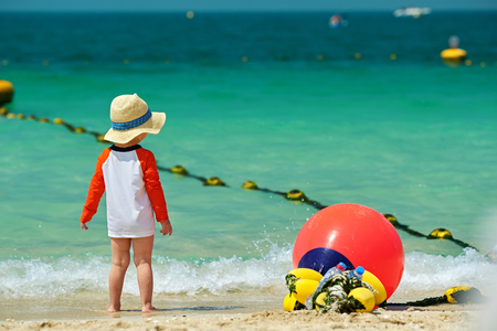 Two year old toddler boy in sun hat walking on beach  Stock Photo