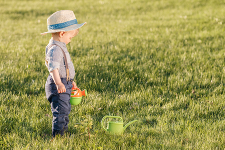 Portrait of toddler child outdoors. Rural scene with one year old baby boy wearing straw hat using watering can Stockfoto