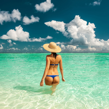 Woman in bikini at tropical beach in Maldives