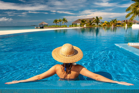 Woman with sun hat at beach pool in Maldives