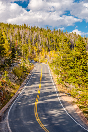 Highway at autumn sunny day in Rocky Mountain National Park. Colorado, USA.  Stock Photo