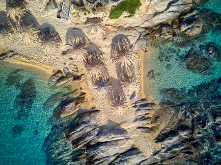 Man in lounger on a beautiful beach aerial view drone shot, Sithonia, Greece
