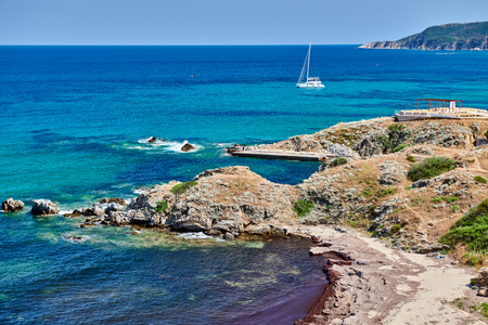 Beach and rocky coastline landscape with yacht , Sithonia, Greece