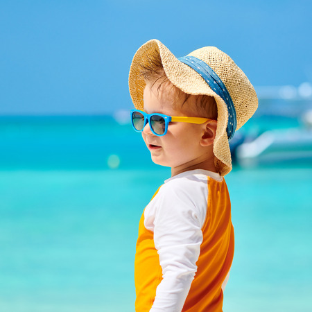 Three year old toddler boy with sunglasses on beach. Summer family vacation at Maldives.