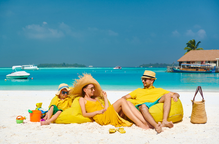 Family on beach, young couple in yellow with three year old boy. Summer vacation at Maldives. Standard-Bild