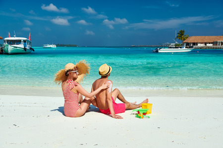Young couple on beach. Woman applying sun screen protection lotion on mans back. Summer vacation at Maldives.