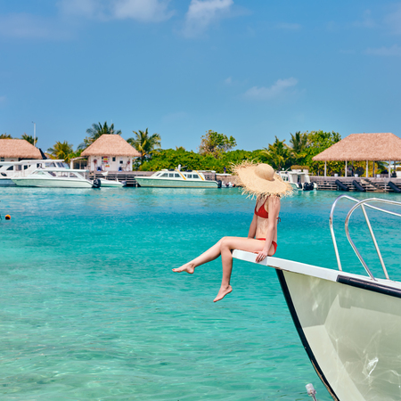 Woman in red bikini sitting on boat bow. Summer vacation at Maldives.