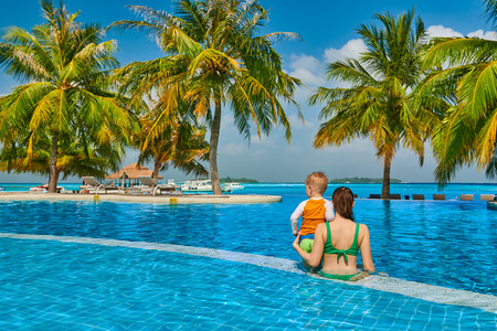 Three year old toddler boy in resort swimming pool with mother. Summer family vacation at Maldives. Stockfoto