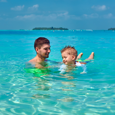 Three year old toddler boy learns to swim with father. Summer family vacation at Maldives.